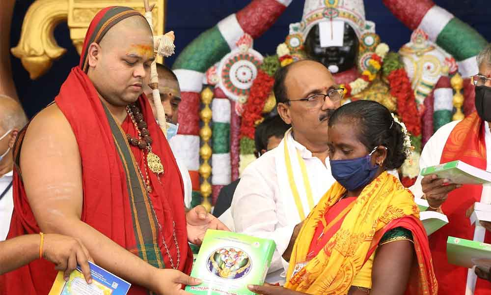Visakha Sarada Peetham Junior Pontiff Sri Swatmanandendra Saraswathi Swami presenting a set of religious books to Dalits and tribals provided by TTD