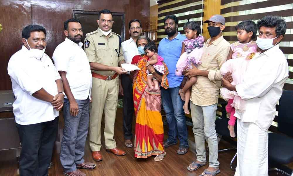SP Fakkeerappa Kaginelli handing over the cheque to the kin of deceased family members, in Kurnool on Saturday.