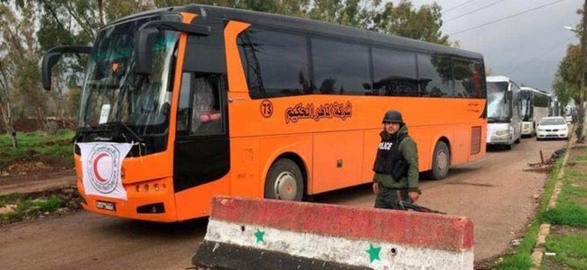 Syrian rebels, families begin leaving Homs district in deal with government