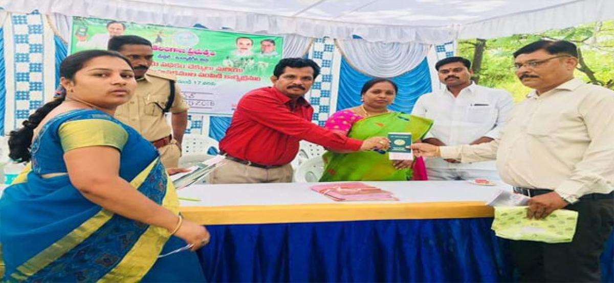 Corporator Sangeetha distributes pattadar passbooks and cheques
