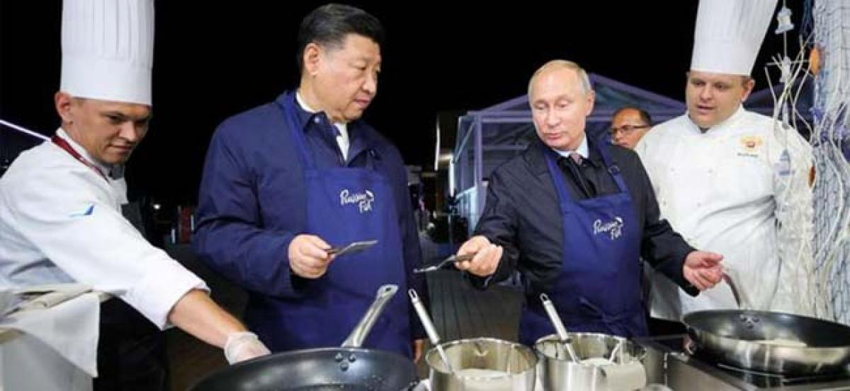 Vladimir Putin, Xi Jinping flip pancakes at Russian economic forum