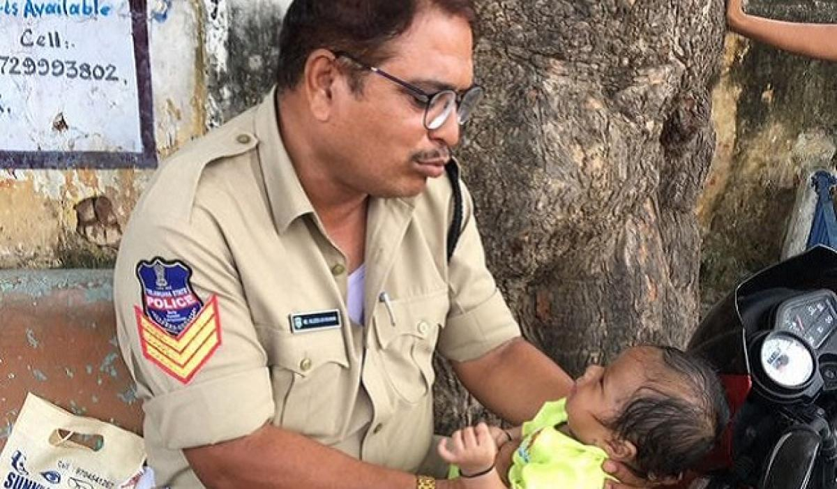 City police consoles baby as mother takes constable exam